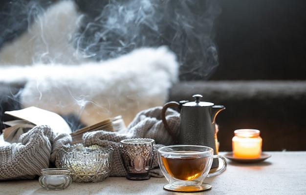 Stilleven met een kopje thee, een theepot en mooie vintage kandelaars met kaarsen op een onscherpe achtergrond.