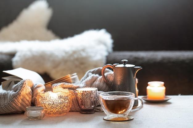 Stilleven met een kopje thee, een theepot en mooie vintage kandelaars met kaarsjes.