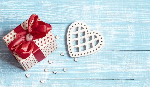 Stilleven met een mooi ingepakt cadeau en decoratieve elementen op een houten ondergrond. valentijnsdag concept vakantie.