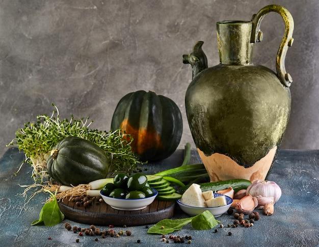 Stilleven met een oude kan, kabocha squash, spruitjes met olijven en kaas op een grijze en een houten standaard