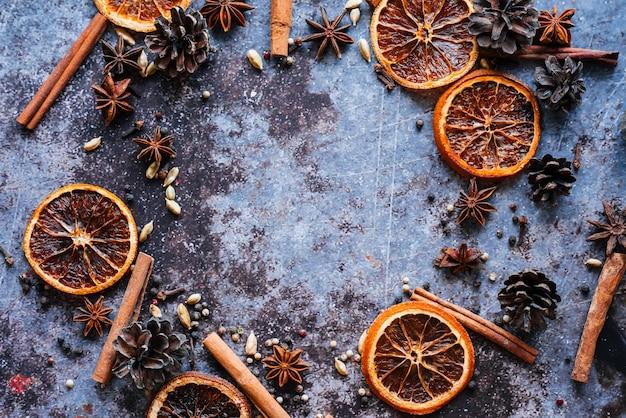Stilleven met een set glühwein. gedroogde sinaasappel, kaneelstokjes, roze peper, kardemom, anijs, kruidnagel op een blauwe achtergrond.