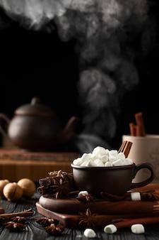 Stilleven met een warme drank met marshmallows en dikke rook over een mok
