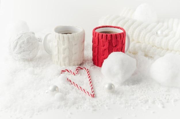 Stilleven met een winterthema met twee mokken thee, hartvormige suikerriet, gebreid decor in witte en rode kleuren