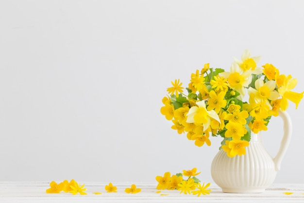 Stilleven met gele lentebloemen in kruik
