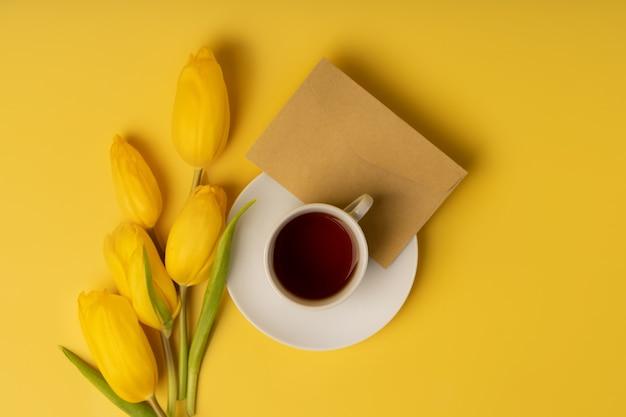 Stilleven met gele tulpen en een mok thee met een envelop op een gele achtergrond