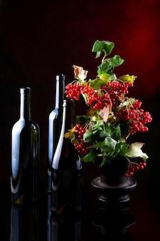 Stilleven met glazen flessen en rode viburnum