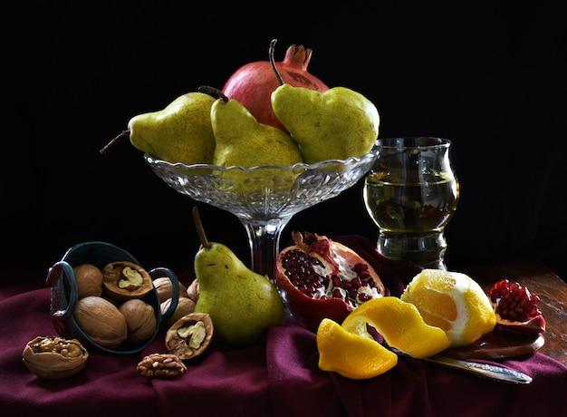 Stilleven met granaatappel, citroen, glas wijn, peer, walnoot. donkere schaduwen, fruit in de stijl van nederlandse kunstenaars.