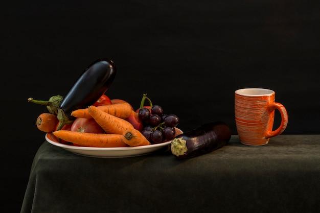 Stilleven met groenten op een bord en een oranje beker