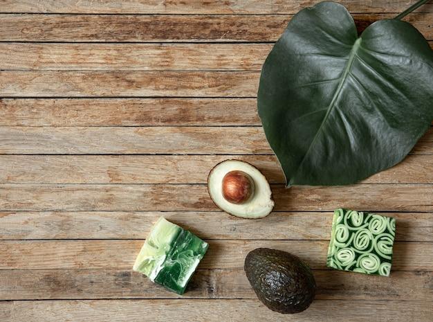Stilleven met handgemaakte zeep, natuurlijk blad en avocado bovenaanzicht. biologische cosmetica en schoonheidsconcept.