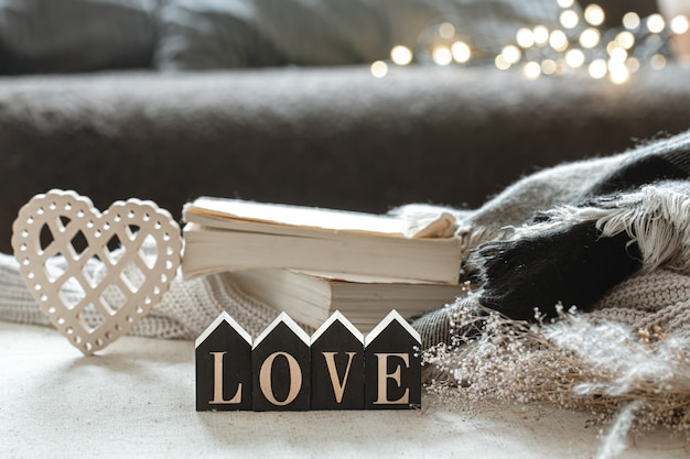 Stilleven met houten woord liefde, boeken en gezellige items op een onscherpe achtergrond met boke.