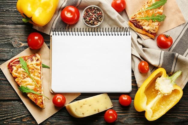 Stilleven met ingrediënten voor pizza en receptennotitieboekje op houten tafel, bovenaanzicht