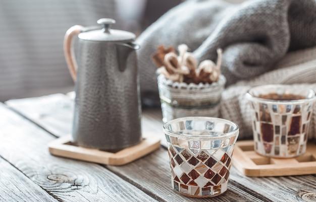 Stilleven met items van het huisdecor, theepotten en een glas thee op een houten tafel in het interieur van de woonkamer, huiselijk concept