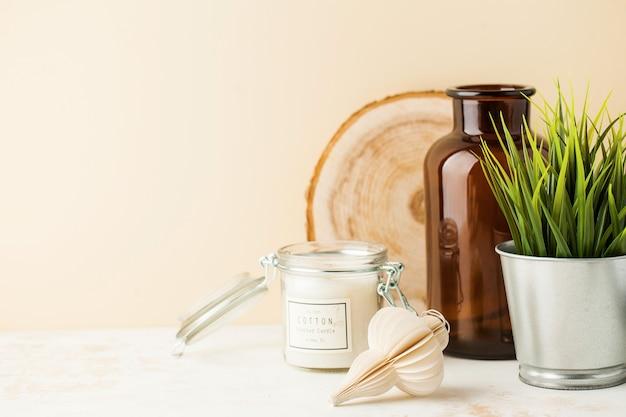 Stilleven met kaars, vaas, groene plant in een pot met ruimte voor tekst