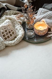 Stilleven met kaarsen in kandelaars, decordetails en gebreide artikelen. het concept van valentijnsdag en huisdecor.