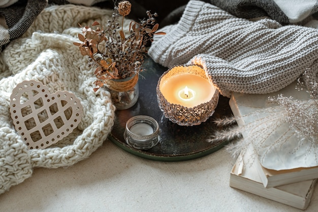 Stilleven met kaarsen in kandelaars, decordetails en gebreide artikelen.