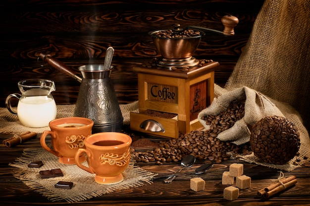 Stilleven met koffiebonen en oude koffiemolen op de houten tafel