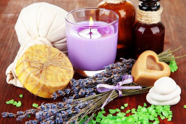 Stilleven met lavendelkaars, zeep, massageballen, flessen, zeep en verse lavendel, op houten tafel op houten oppervlak