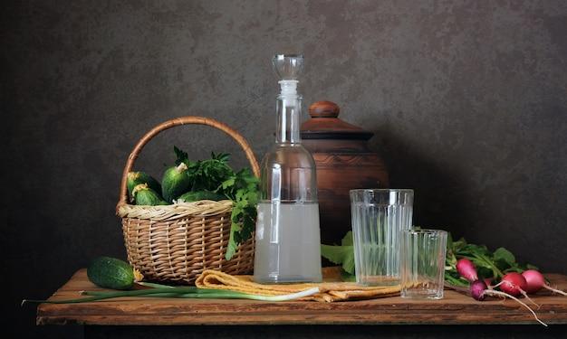 Stilleven met maneschijn in de fles, radijs en verse komkommers op de tafel.
