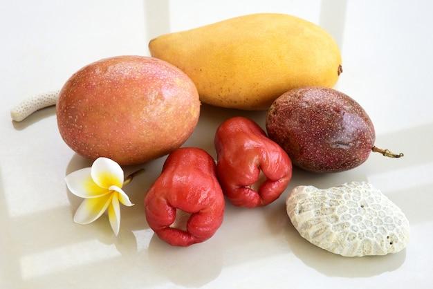 Stilleven met mango, passievrucht en cashewappelen.