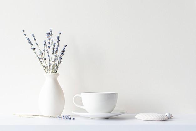 Stilleven met minimale compositie lavendel gedroogd boeket keramische witte kop en warme drank thee of koffie ochtendstemming in beige toon