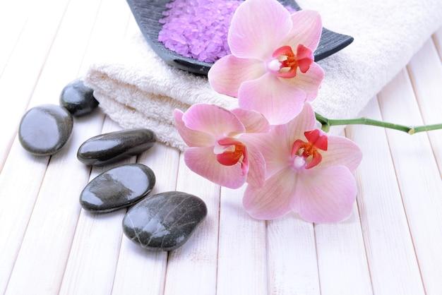 Stilleven met mooie bloeiende orchideebloem, handdoek en kom met zeezout, op houten kleurentafel