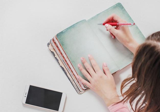 Stilleven met open ontwerpersnotitieboekje, vrouwenhanden met pen en