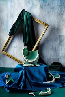 Stilleven met overblijfselen van gebroken groenblauw gekleurde vaas, groen en blauw fluweel en fotolijst los van de muur