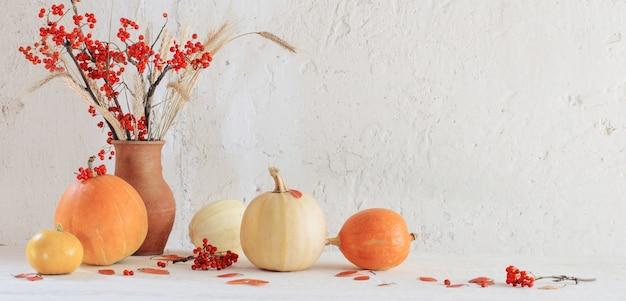Stilleven met pompoenen en rowan takken op houten tafel