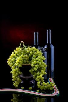 Stilleven met rijpe druiven en glazen flessen