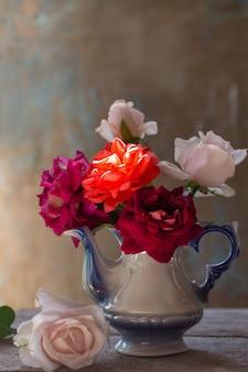 Stilleven met roos in oude theepot