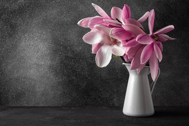 Stilleven met roze magnolia bloemen boeket in vaas op zwarte ondergrond