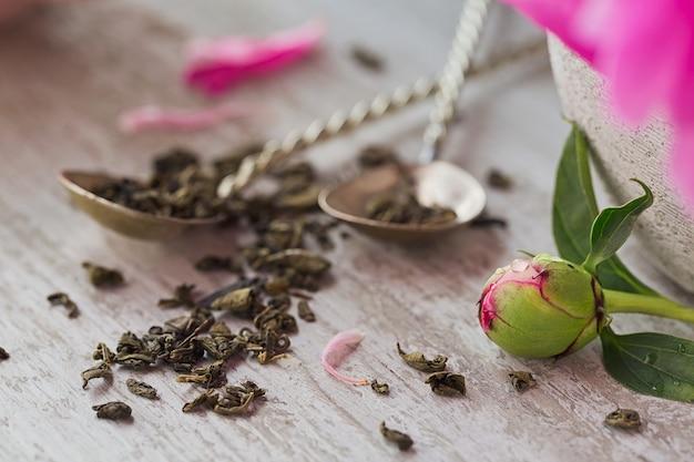 Stilleven met roze pioenbloemen en een kopje kruiden- of groene thee op rustieke houten achtergrond