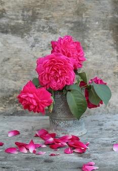 Stilleven met roze rozenbloem in zilveren vaas op grunge houten ruimte