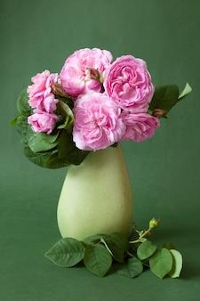 Stilleven met roze rozenbloemen in vaas op groen