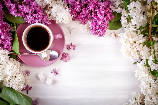 Stilleven met takken van lila en een kopje koffie op een houten tafel.