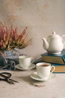 Stilleven met thee, boeken en bloemen