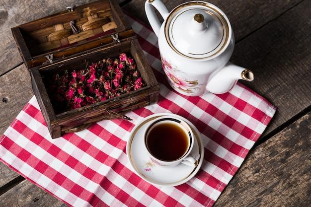 Stilleven met theekop en tafelkleed op houten lijst