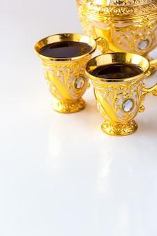 Stilleven met traditionele gouden arabische koffie die met dallah en kop thee wordt geplaatst.