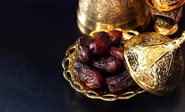 Stilleven met traditionele luxe gouden arabische koffie die met jezva, kop en data wordt geplaatst. ramadan concept.