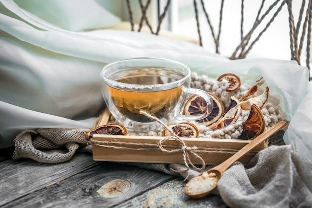 Stilleven met transparante kopje thee op houten tafel