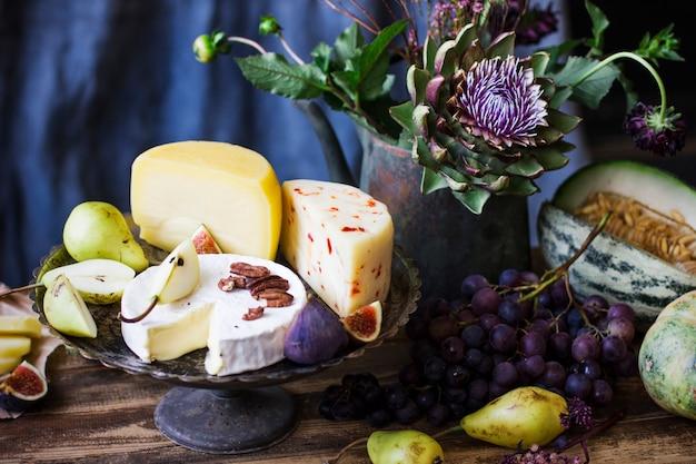 Stilleven met verschillende kaas, vers fruit en tuinbloemen