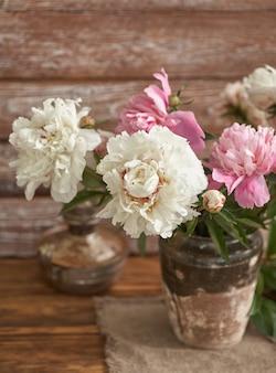 Stilleven met witte en roze pioenrozen in een oude keramische vaas op houten achtergrond