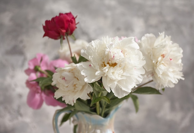 Stilleven met witte en roze pioenrozen in een witte vaas