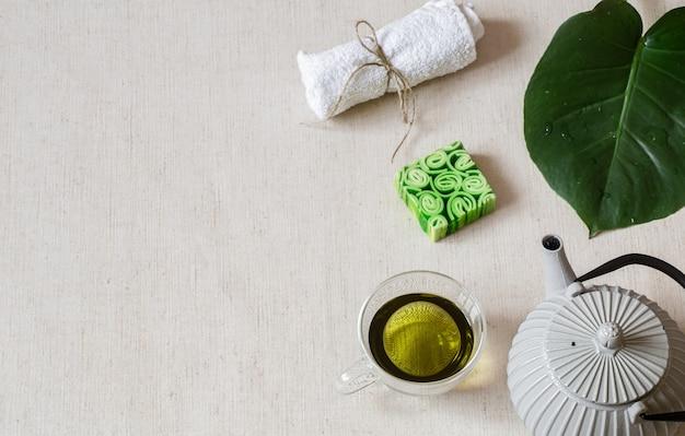 Stilleven met zeep, handdoek, blad en groene thee exemplaarruimte. gezondheid en schoonheid concept.