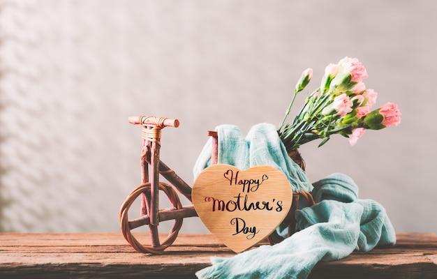 Stilleven met zoete anjer bloemen in houten fiets op houten tafel, moederdag concept met een bericht voor happy mother's day op een houten hart