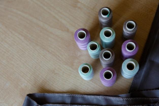 Stilleven naaibenodigdheden draad en stof op een houten tafel