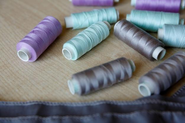 Stilleven. naaibenodigdheden. draden en stof liggen op houten tafel