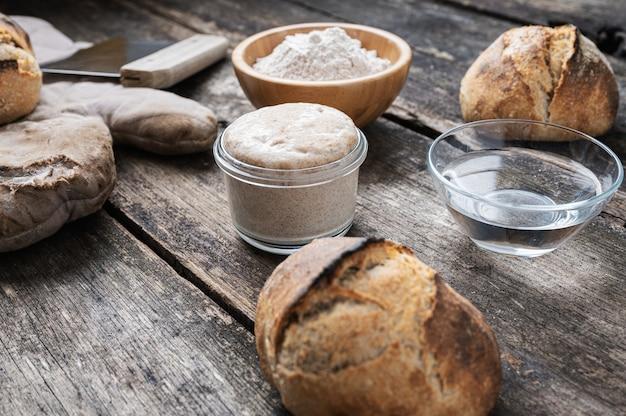 Stilleven setting van zuurdesem startergist en broodingrediënten op rustieke houten bord.