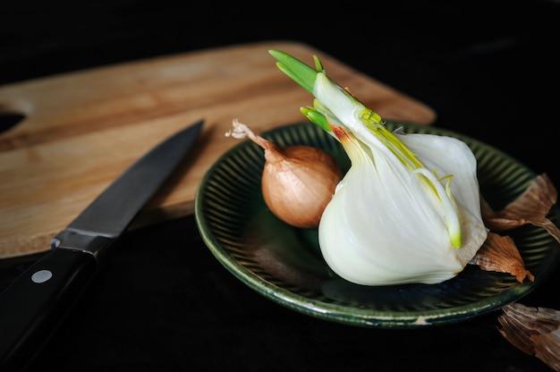 Stilleven. uien op een bord. er is de helft van de ui schoongemaakt van een schil en een kleine ui ligt op een bord. achter is een mes en een snijplank.