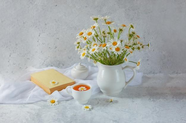 Stilleven vaas met madeliefjes een kopje thee en een oud boek op een lichte achtergrond